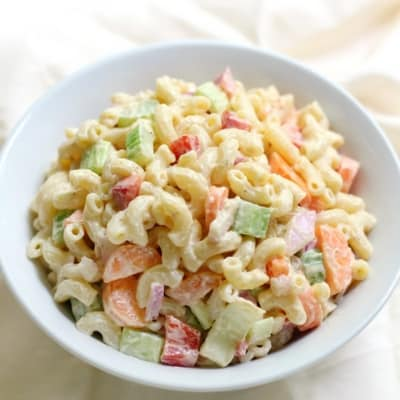 Colorful macaroni salad in white dish - Memorial day side dishes we love