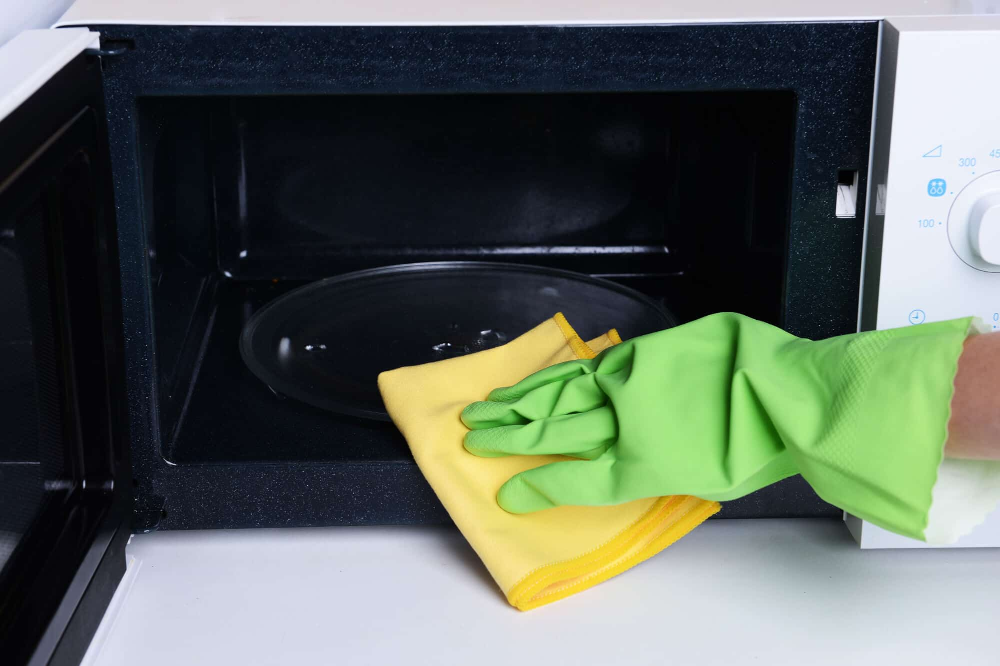 woman wiping microwave with towel while wearing gloves; displaying a great house cleaning hack