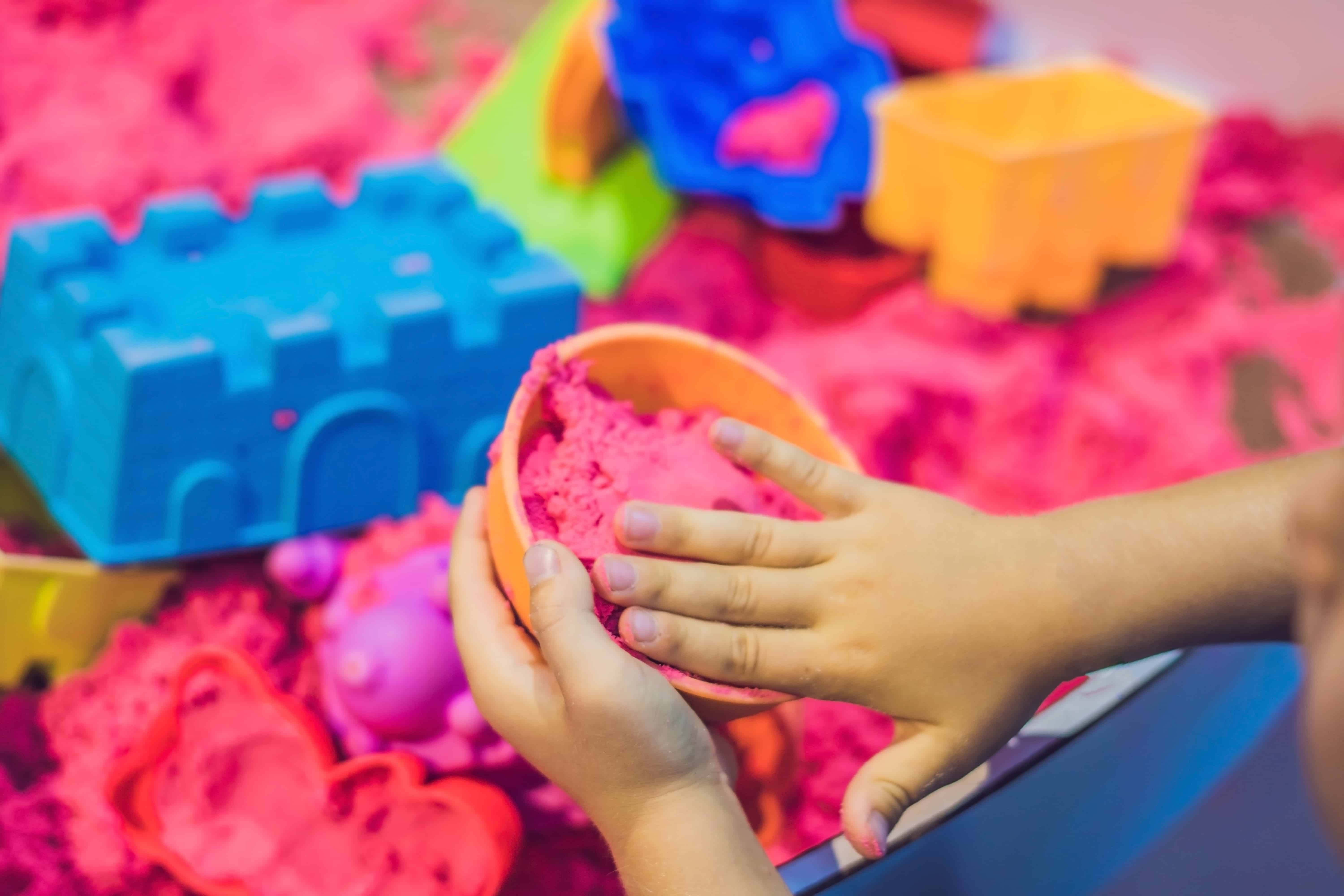 Child's hands molding kinetic sand into shape from kinetic sand play set