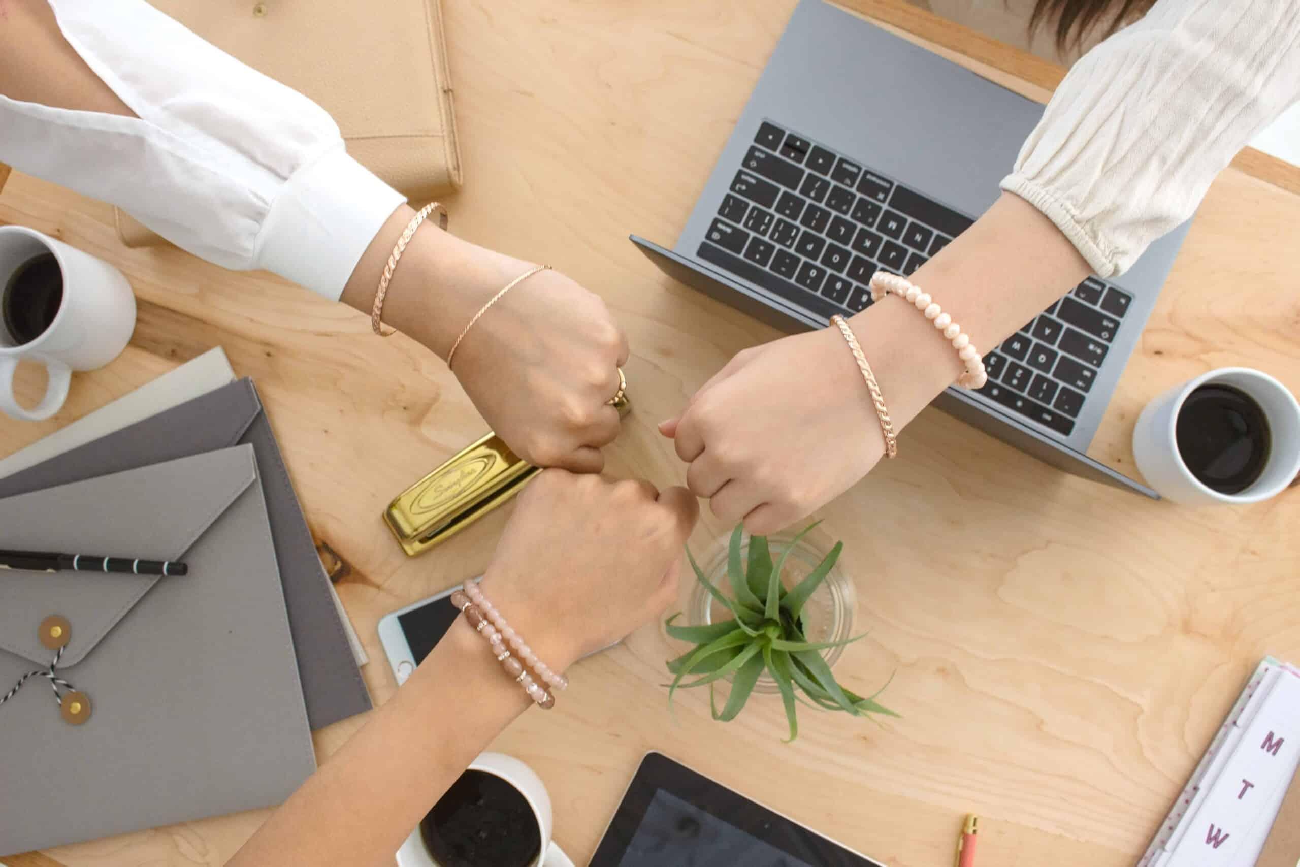 Female entrepreneurs celebrating success over table.