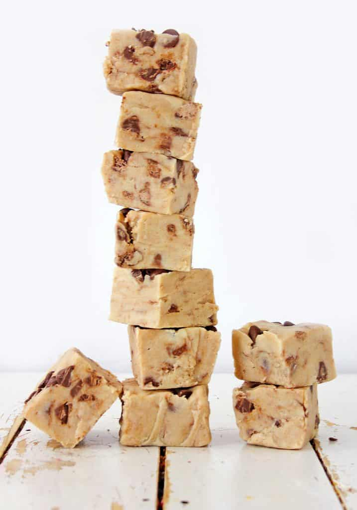 cookie dough fudge squares stacked on top of each other on wooden table top