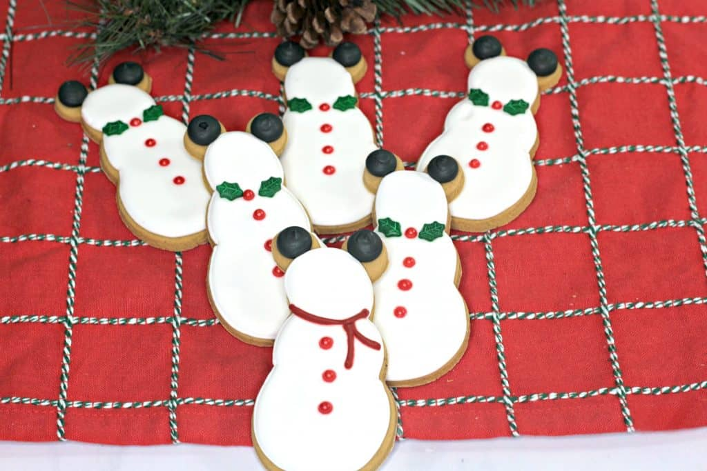Mickey snowman gingerbread cookies on plaid tablecloth