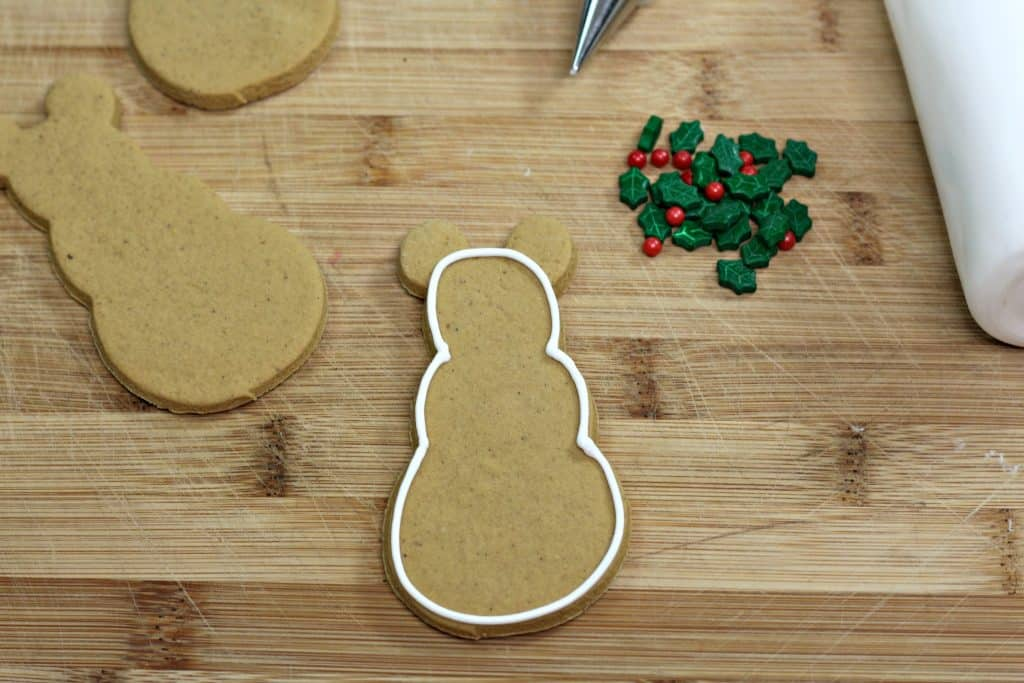Gingerbread snowman on counter being outlined with white frosting.