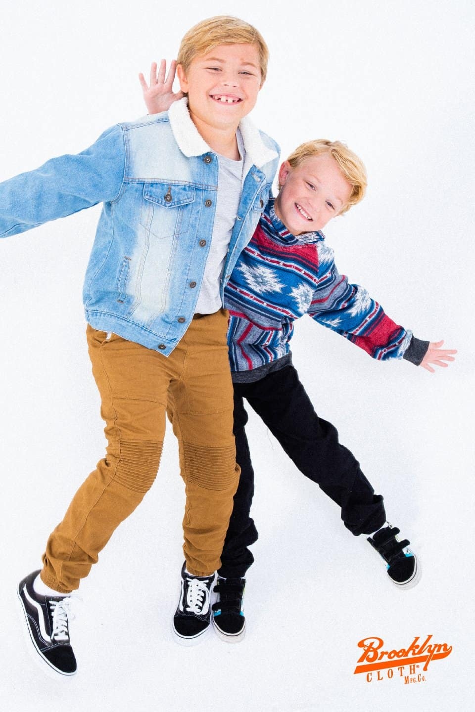 Two boys in stylish clothes hugging each other