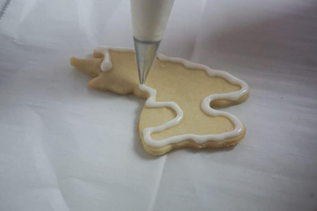 llama cookies being iced on parchment paper