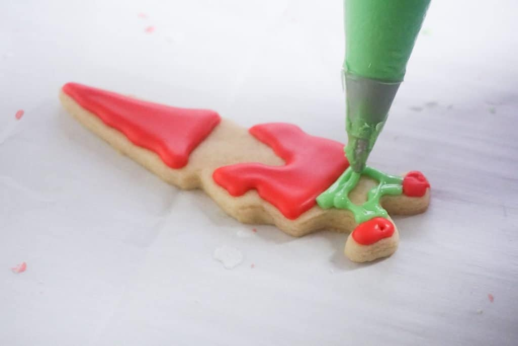 Green icing in piping bag being dispensed onto legs of gnome cookie to make pants.