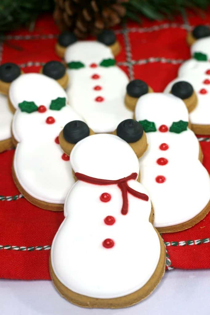 Decorated gingerbread snowman cookies on plaid tablecloth.