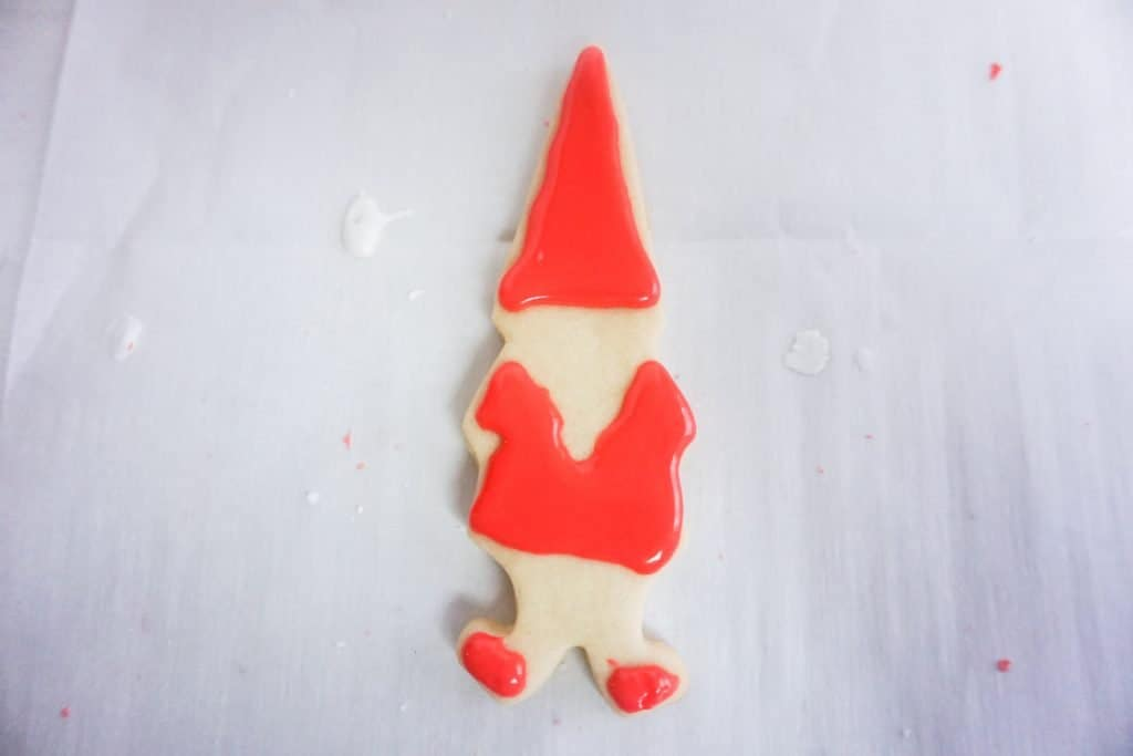 Gnome cookie with red icing on body, hat, and shoes.