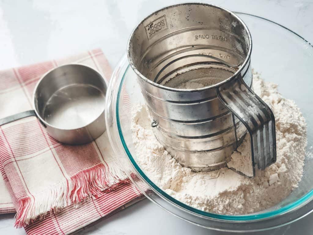 Flour sifting in bowl of sifted flour.