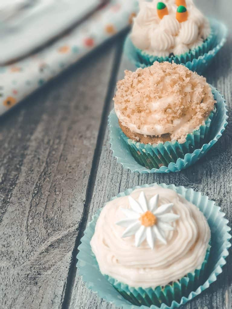 3 decorated carrot cake cupcakes in blue cupcake liners on wooden table.