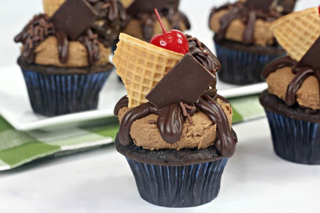 Chocolate cupcakes topped with cookie dough, ganache, hershey bar and waffle cone piece sitting on countertop.