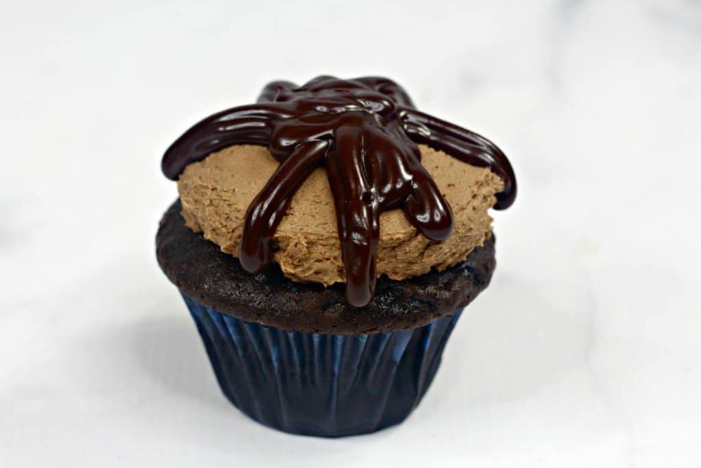 Chocolate cupcake iced with homemade chocolate frosting on marble countertop with ganache added on top