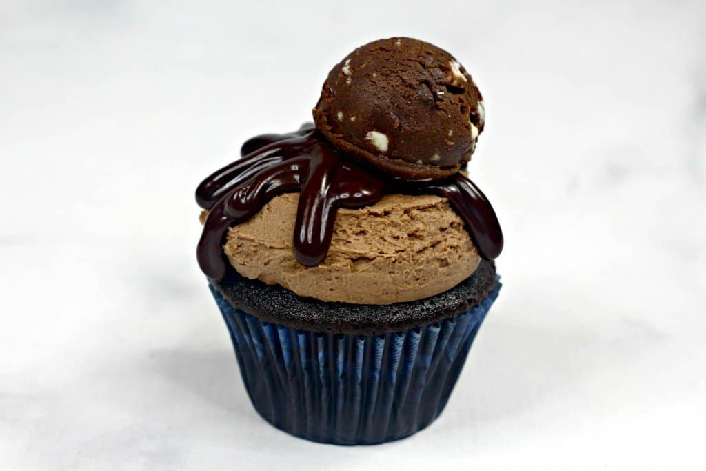 Chocolate cupcake iced with homemade chocolate frosting on marble countertop with ganache and cookie dough on top.