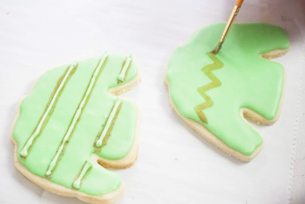 Green ugly sweater cookies on parchment paper having lines drawn on for decoration