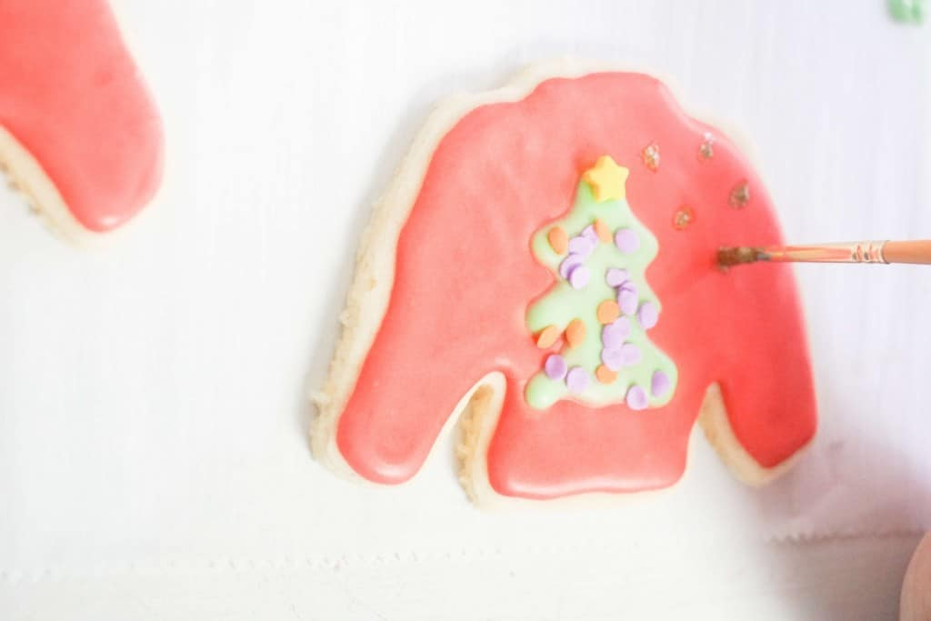 Ugly sweater cookie on parchment paper with icing buttons being added by brush