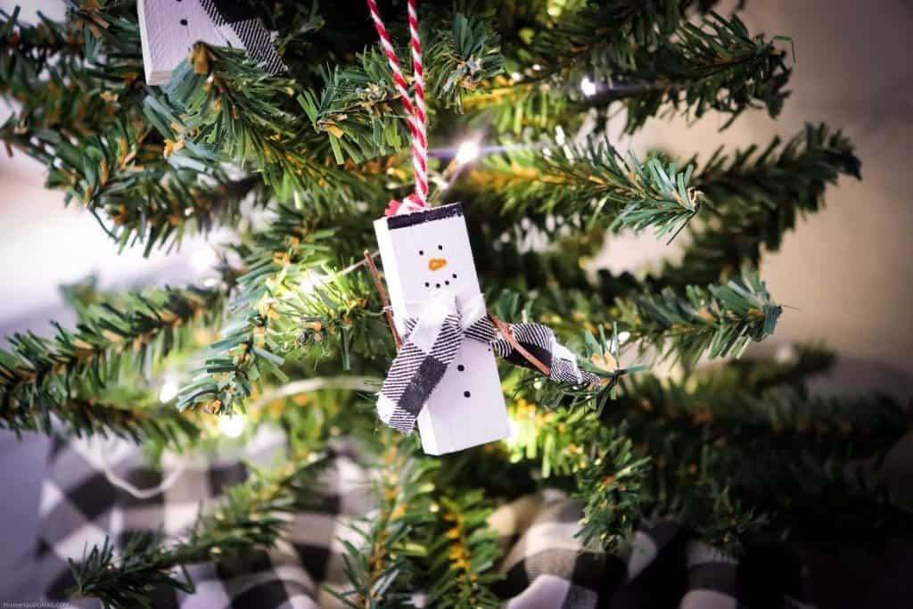 Snowman ornament made from jenga piece hanging from tree