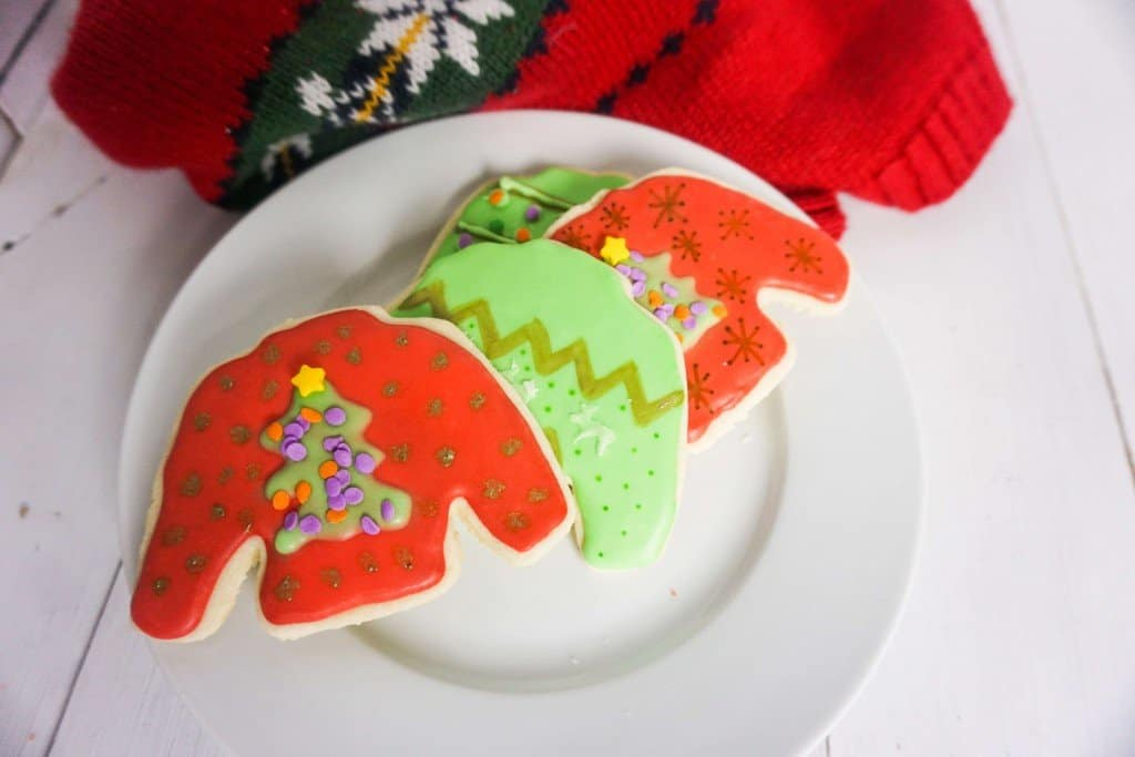 4 Ugly sweater cookies in various designs spread out on white plate - sitting on white wooden table