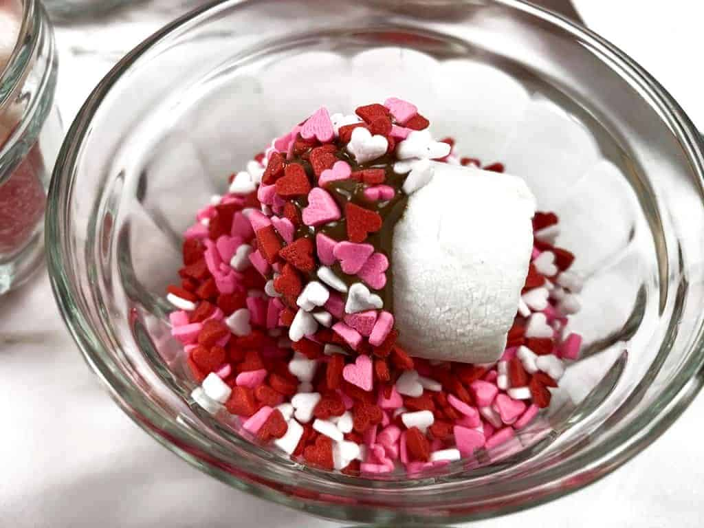 Marshmallow in a bowl of sprinkles, being covered to be added to candy kabobs.
