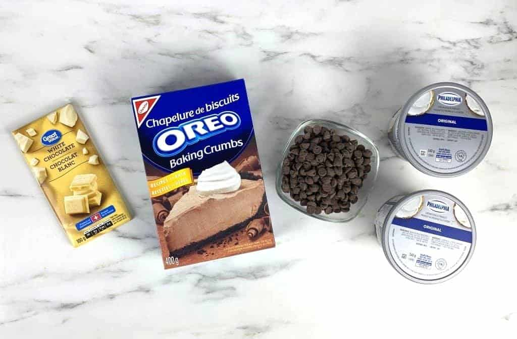 Ingredients for oreo truffles laid out on marble counters. Includes oreo crumbs, white chocolate, milk chocolate, and cream cheese.