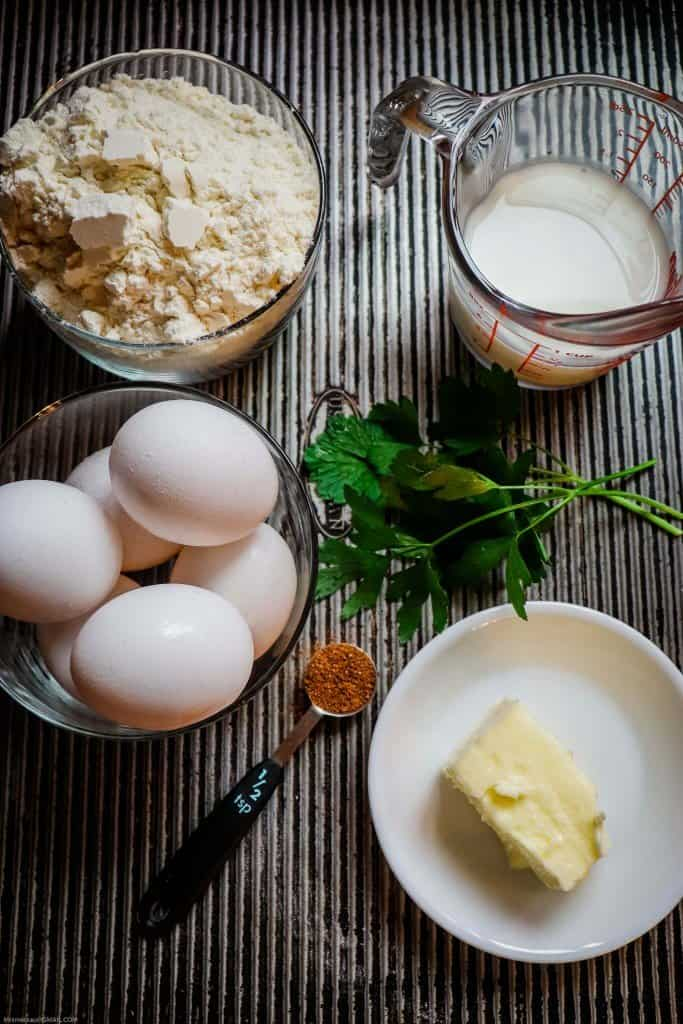 Ingredients for making homemade spaetzle. Milk, flour, eggs, butter, and parsley on table.