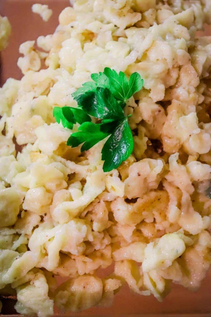 Finished homemade spaetzle on a plate with parsley as a garnish.