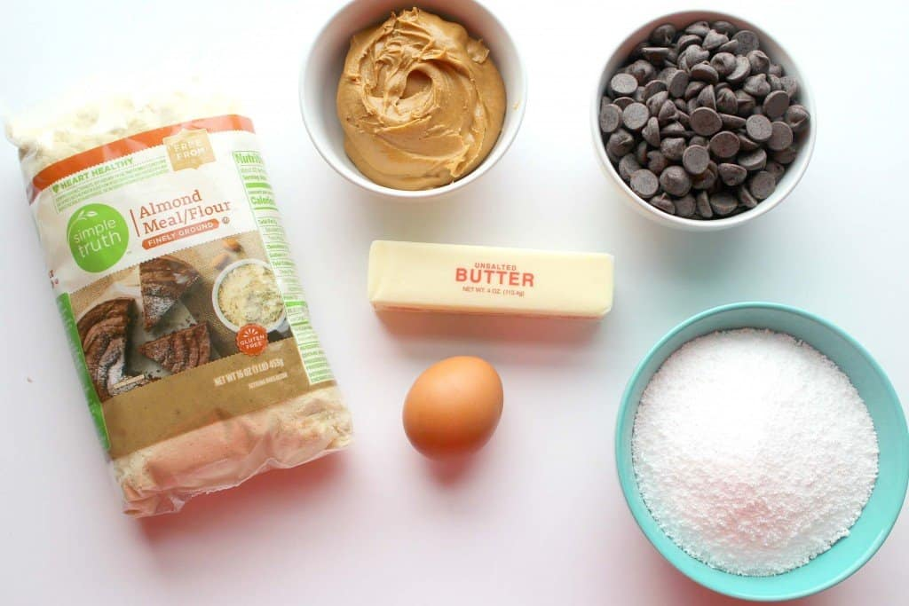 Ingredients necessary for keto tagalongs consisting of almond flour, butter, egg, peanut butter, swerve, and dark chocolate.