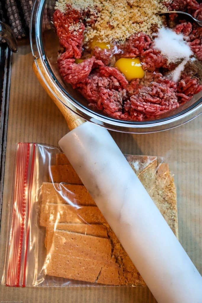Swedish meatball ingredients being combined in glass mixing bowl. Rolling pin being used to crush graham crackers in ziploc bag.