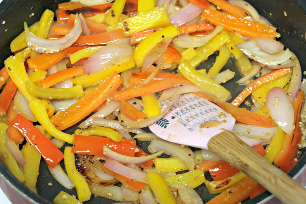 Veggies being sauteed in skillet with spatula to make Cajun creamy chicken pasta.
