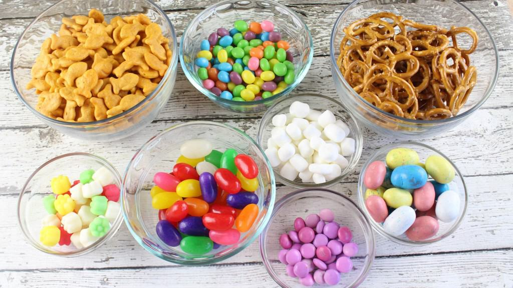 Spring snack mix ingredients laid out on table in glass bowls.