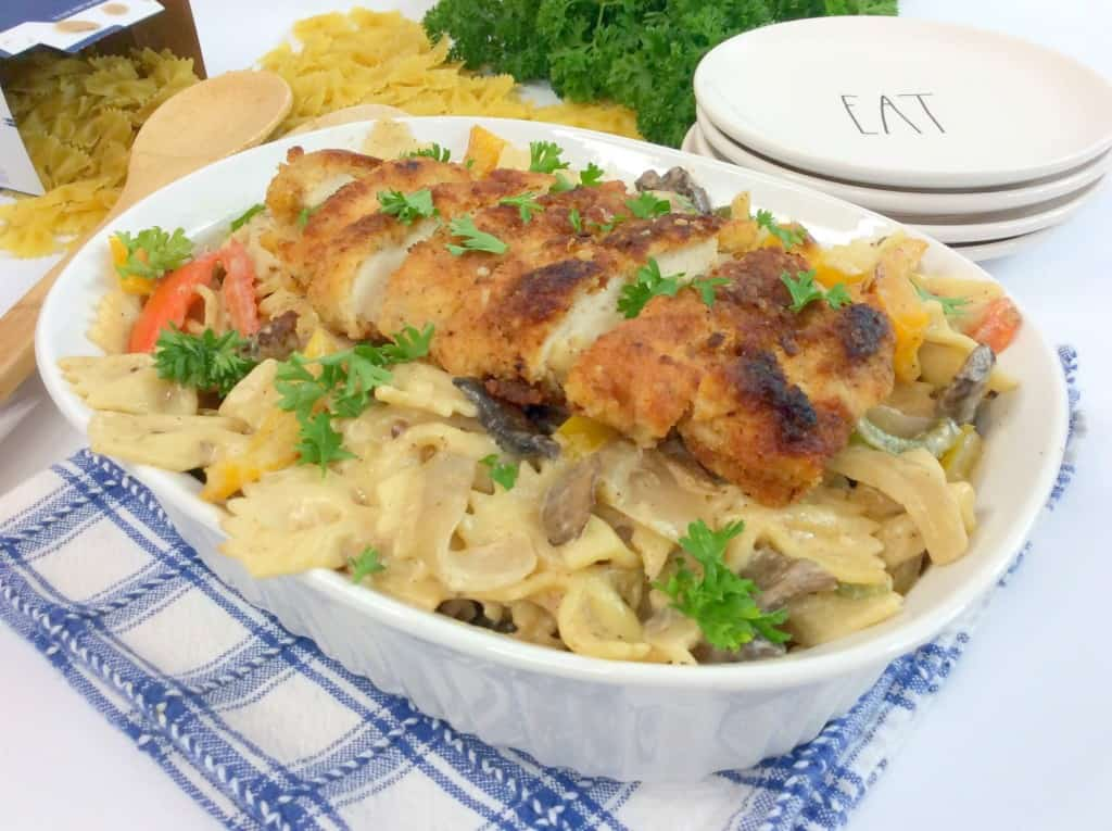 Cajun creamy chicken pasta in white dish on blue towel