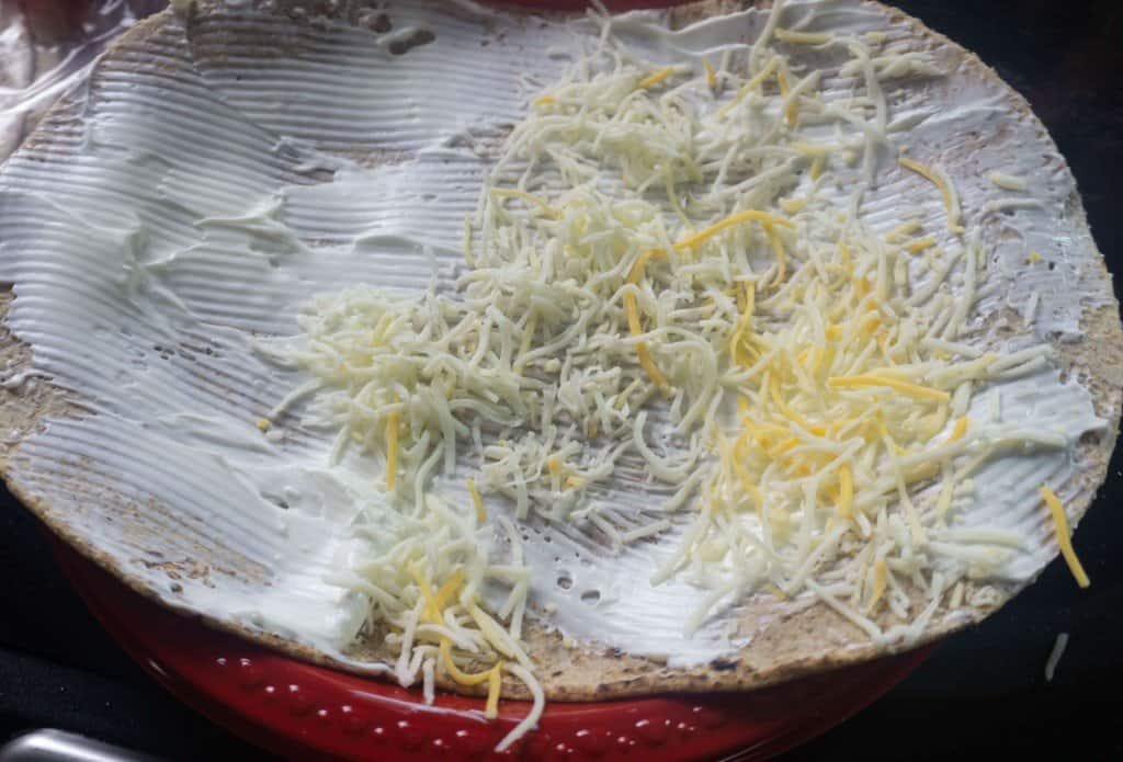 Tortilla with sour cream and shredded cheese being prepared for chicken guacamole wraps.