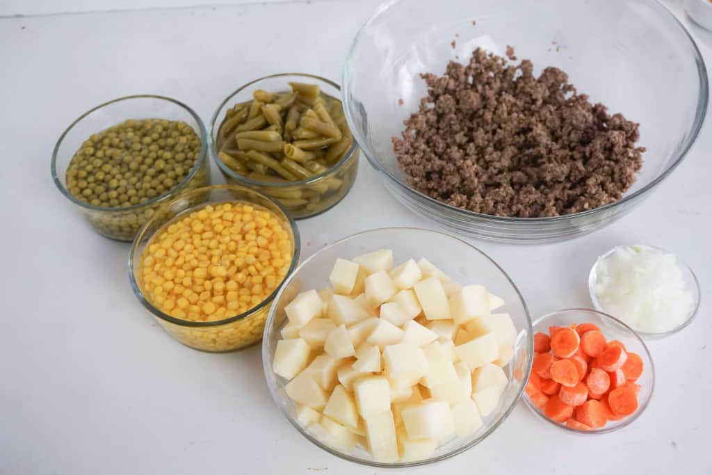 Ingredients for hamburger potato soup placed in glass bowls on white counter top.