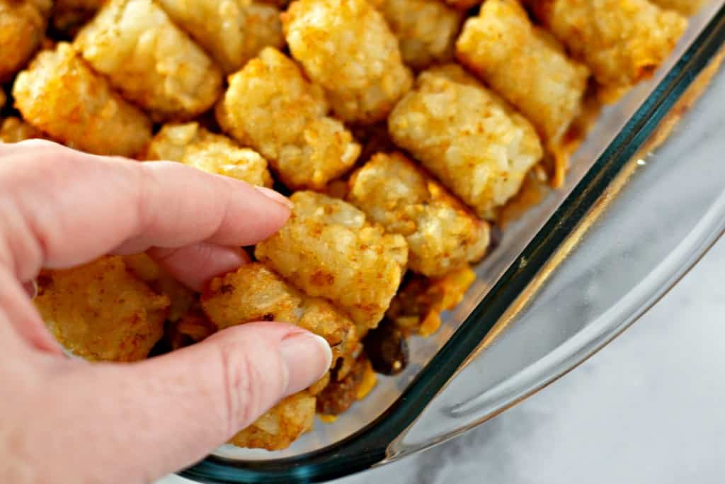 Mexican Tater Tot Casserole being assembled prior to baking.