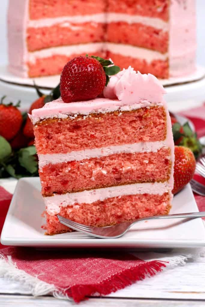 Slice of 3-layer strawberry cake sitting on white plate on wooden countertop with fork on the plate.