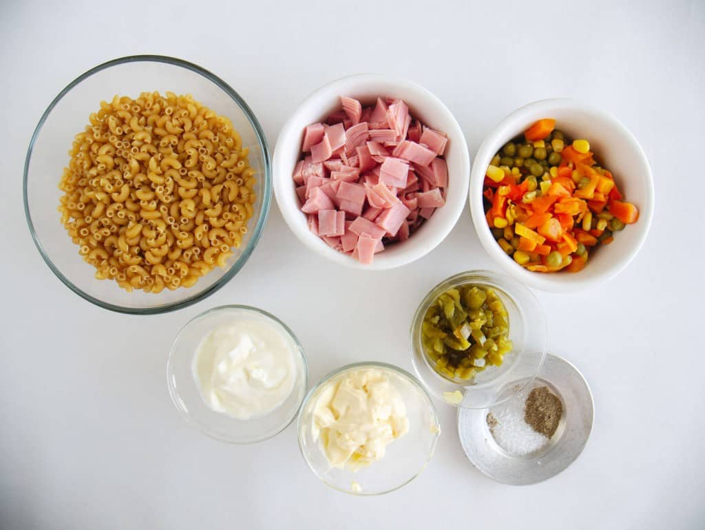 Macaroni Salad ingredients on counter in individual bowls. Salt/pepper, mayo, sour cream, veggies, ham, macaroni noodles, peppers.