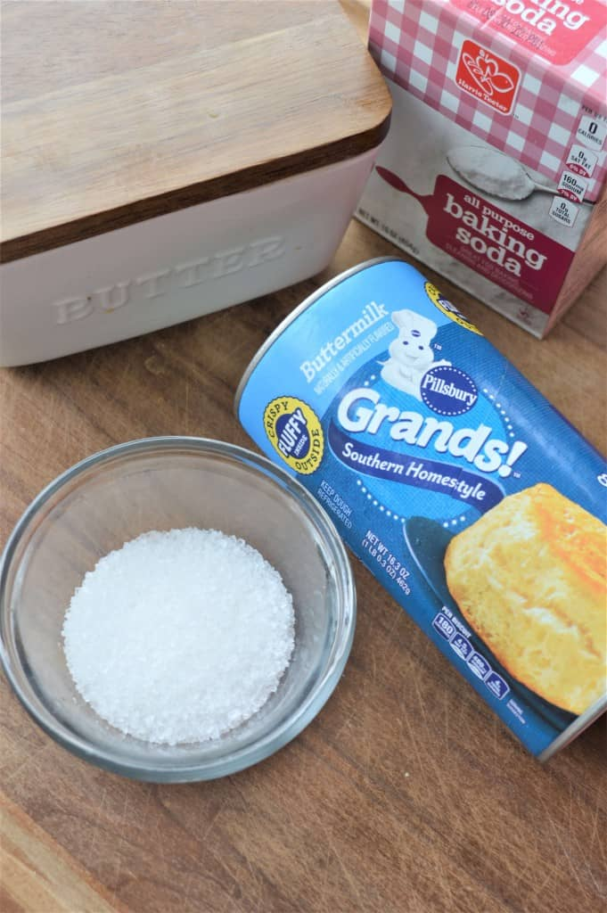 Clear glass bowl of salt on counter top next to can of biscuits